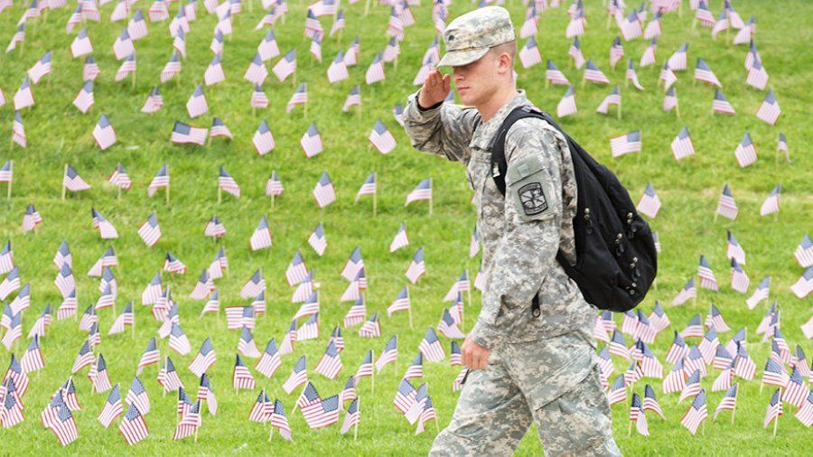 A military student salutes as he walks past a collection of american flags in the ground