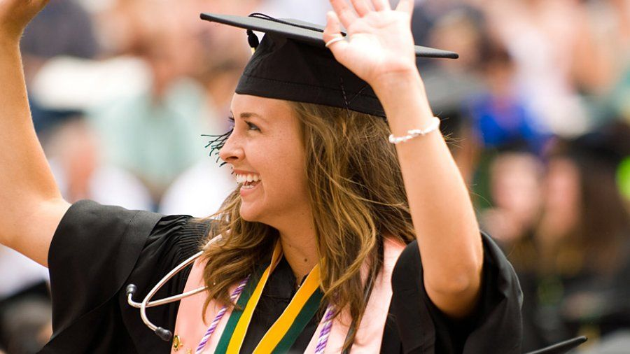 A nursing graduate waves to the crowd at Commencement.