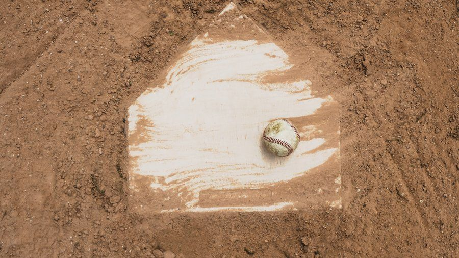 Homeplate of a baseball field with a baseball on it, surrounded by dirt.