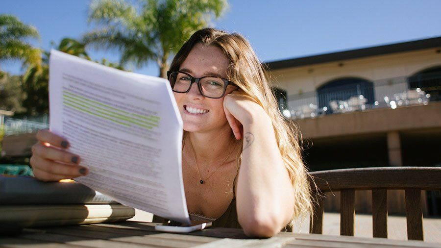A female PLNU student sits at Sunset Deck studying notes for an upcoming class.