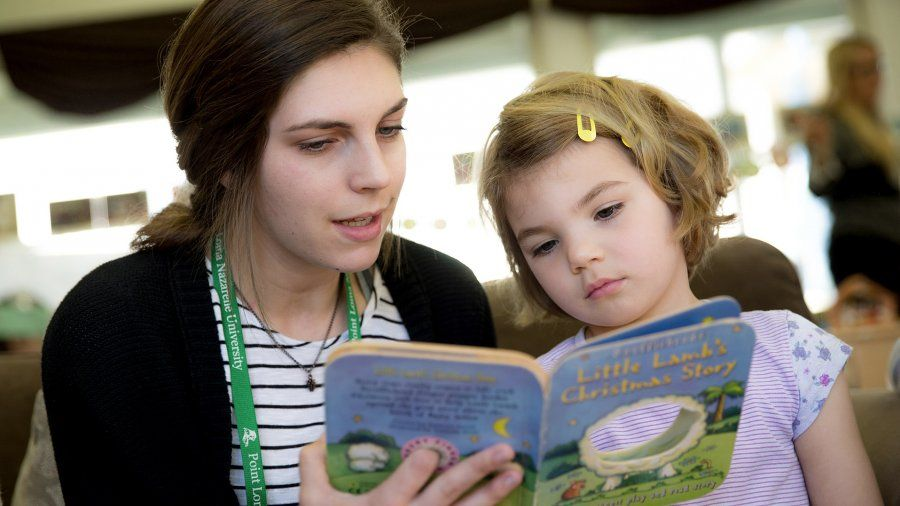 A female college student reads a children's book to a young girl inside