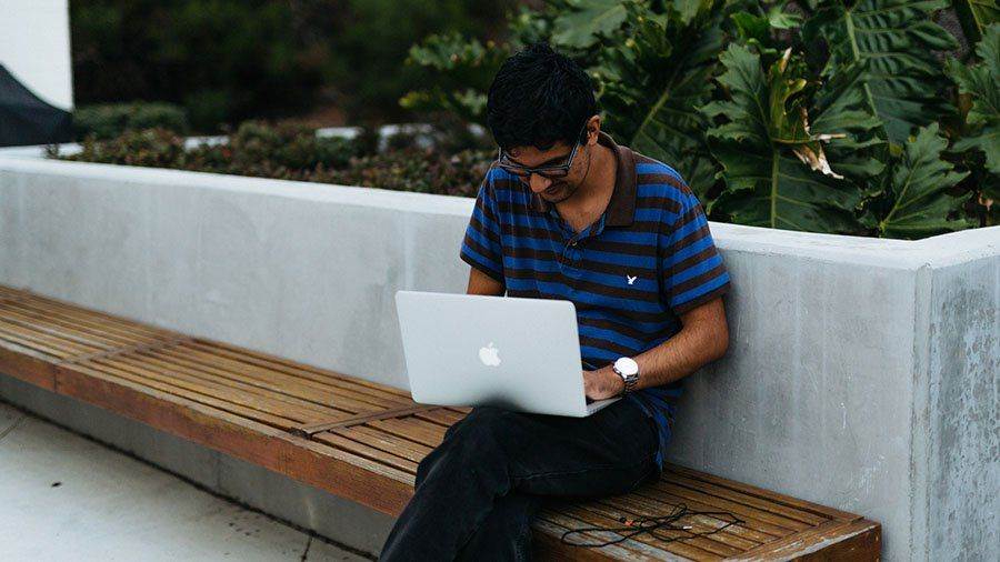 A male student sits on an outside bench and works on his laptop.
