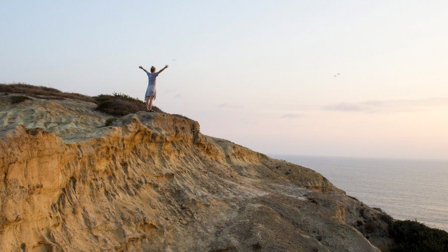A PLNU student spreads her arms and watches the sunset on the San Diego cliffside.