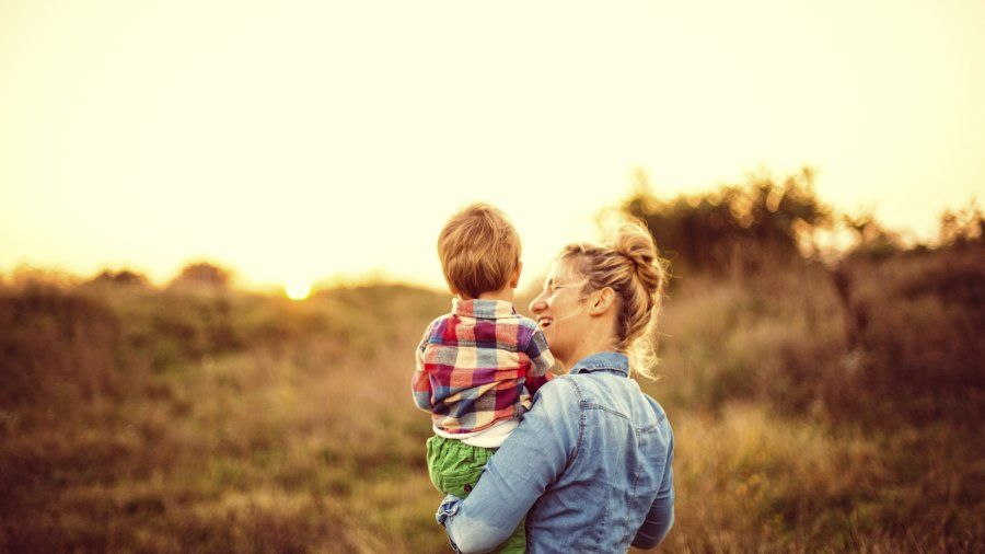 stock image of woman holding child in field