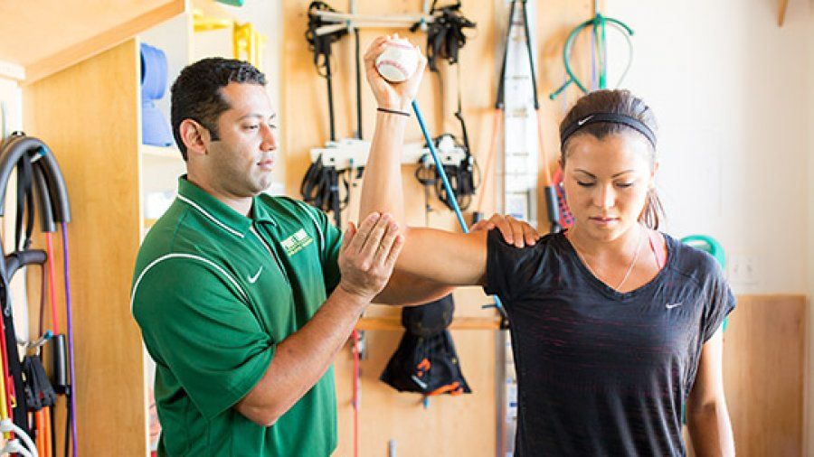 A PLNU athletic trainer helps a student stretch.