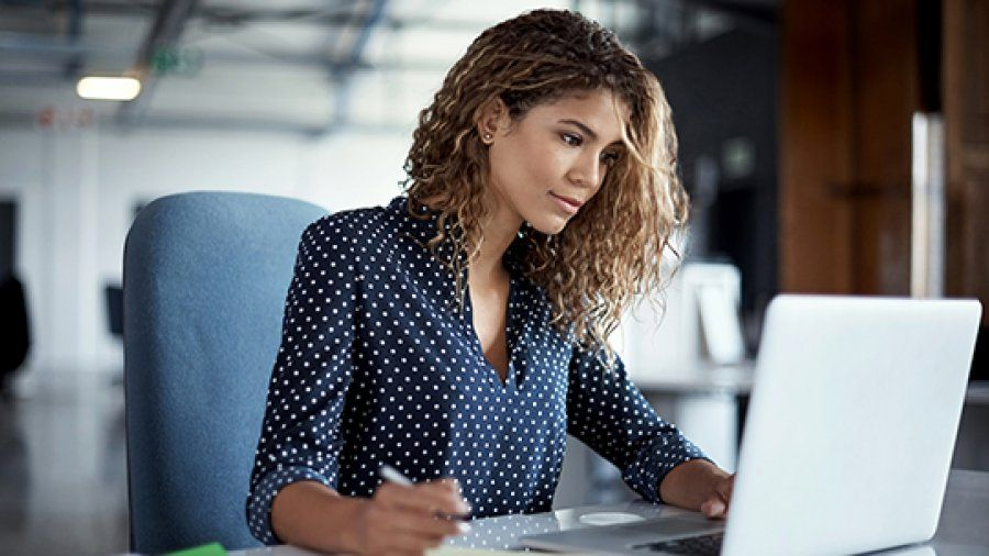 A female working professional looks at her computer and works in a large industrial office.