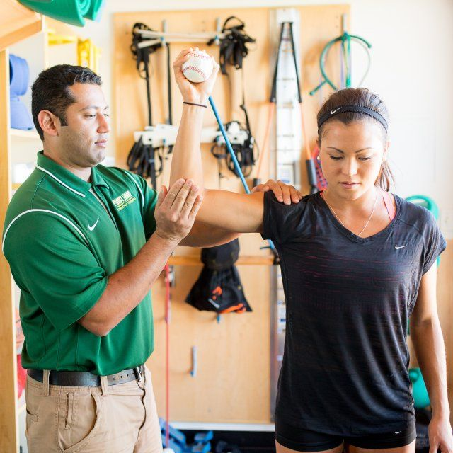 An athletic trainer helps a female athlete stretch her right shoulder