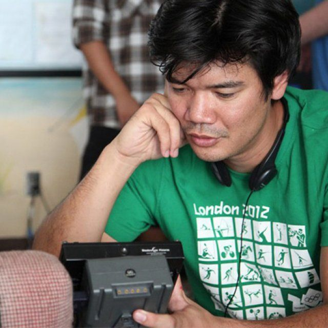 Male in green shirt and headphones around his neck looks into a camera viewfinder and replays a scene just filmed