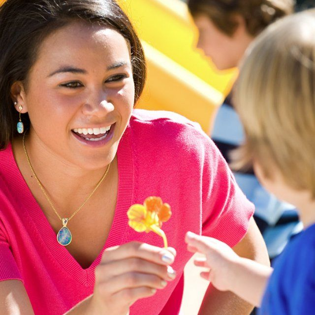 A female ECLC student worker hands a small orange flower to a child in the playground
