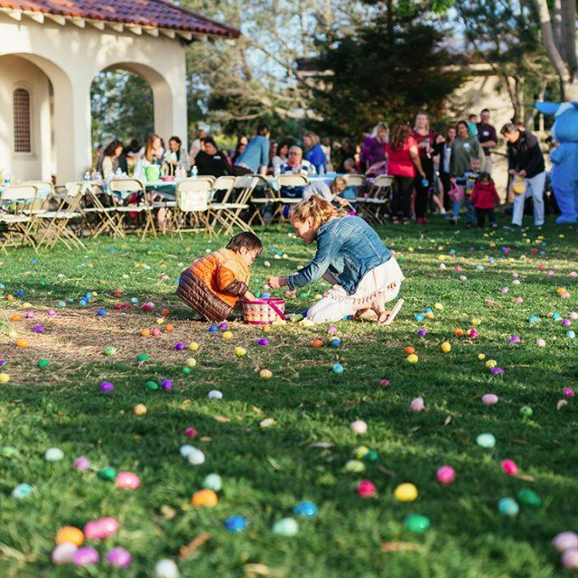 A PLNU student helps a child search for easter eggs on alumni lawn