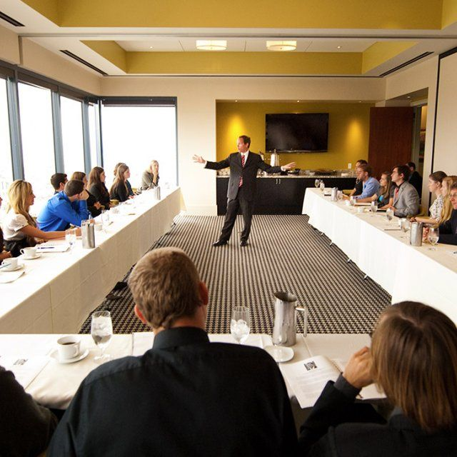 A speaker in a business suit presents in a conference room during a breakfast event.