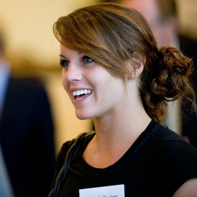 Female student smiling as she listens to a presentation during at Toast at the Point