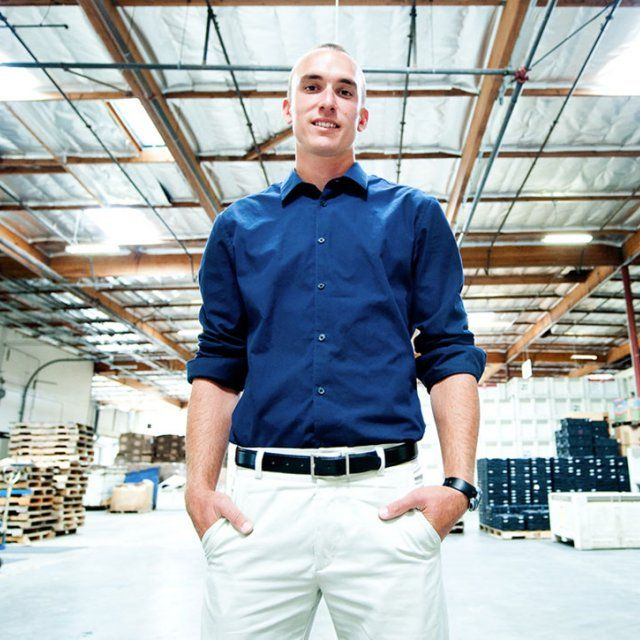 Man in blue shit and white pants standing with his hands in his pockets in a warehouse