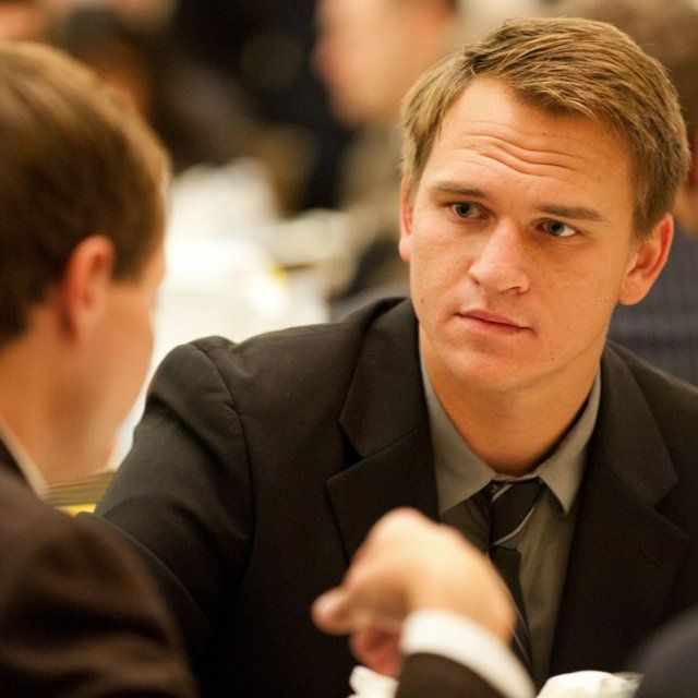 Two male students wearing suits deep in conversation at an MBA executive development event
