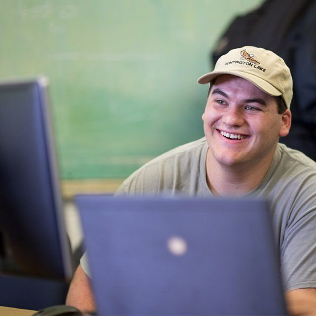 Student smiles while seated behind a computer