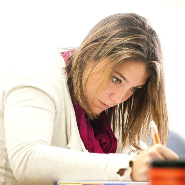 A focused female student writes down notes in class wither her pencil