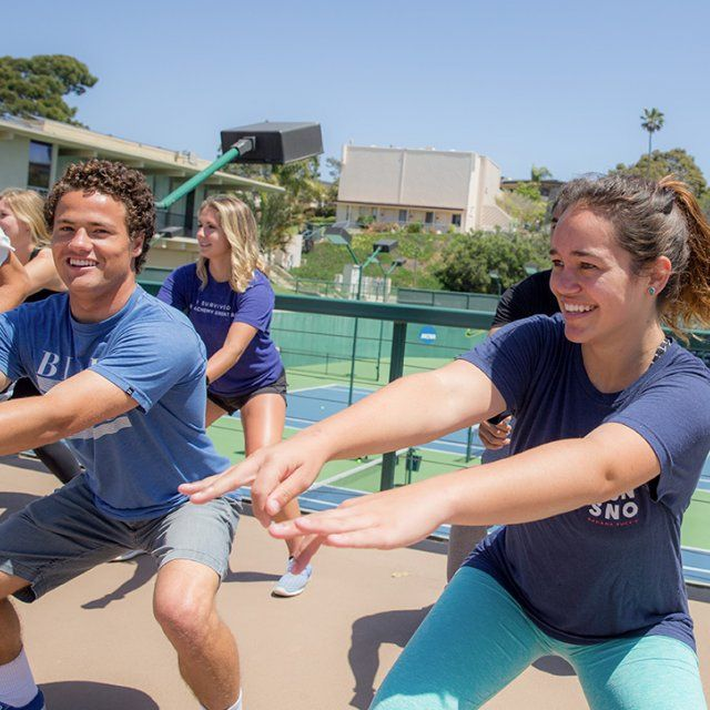 Students bust a move in an outside aerobic dance class.