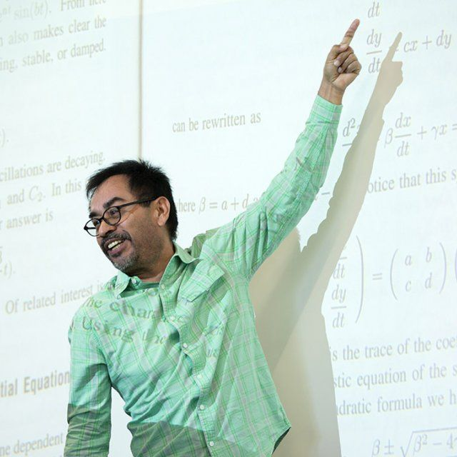 Professor Jesus Jimenez works on a math problem in class