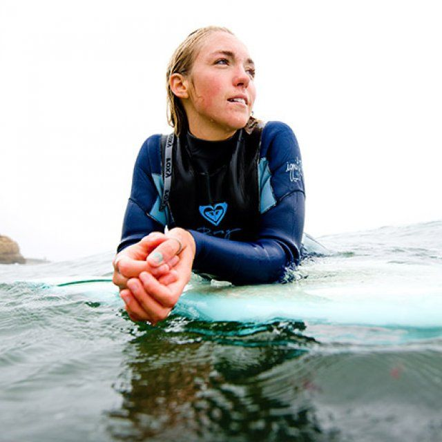 Molly Guldin looks out for the next wave coming in while surfing off Sunset Cliffs.