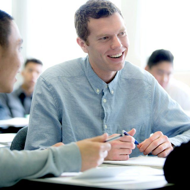 A student smiles while working in group in class.