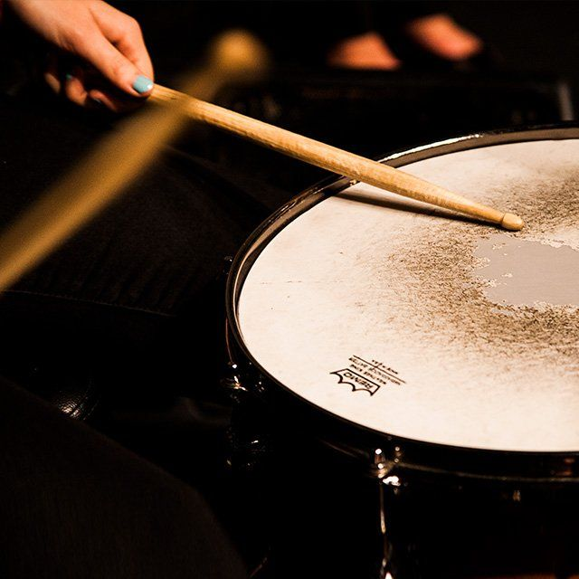 A pair of hands holding drumsticks hit a snare drum to a beat.