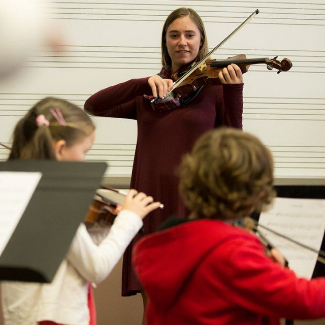 A student teaches children violin through the Point Loma String Project
