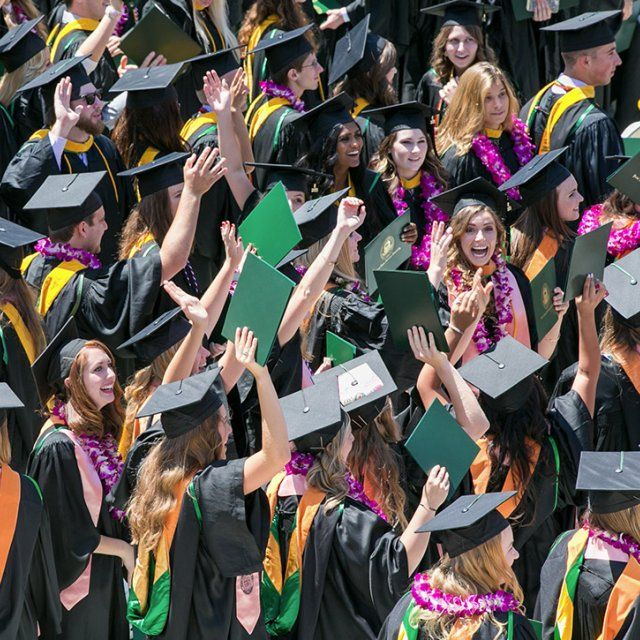 PLNU students in cap and gown celebrate receiving their diplomas during commencement