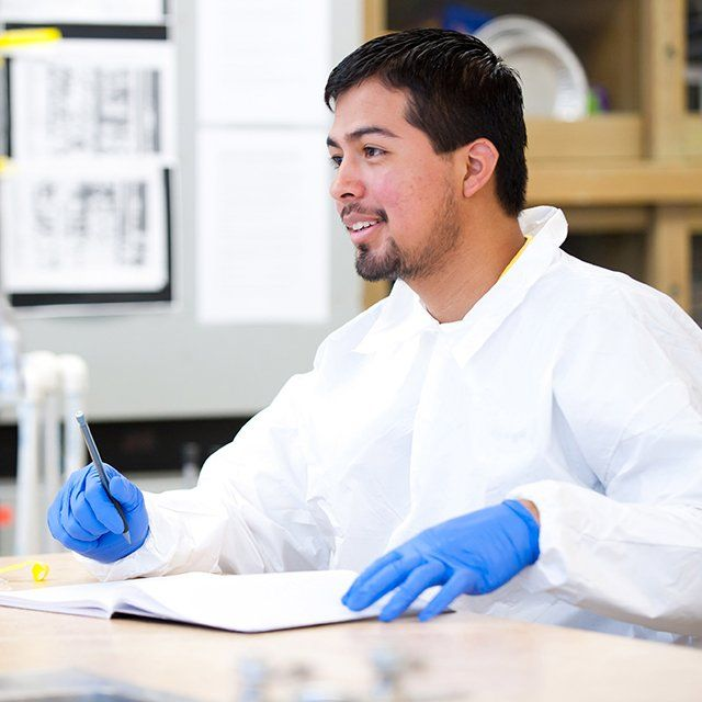 A student wearing a lab coat and safety gloves writes down his observations.