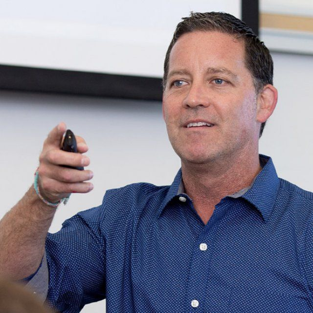 Randal Schober teaching class with a powerpoint clicker in his hand