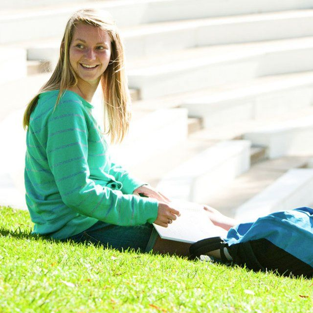 Female student sitting on the grass outside of the Greek Amphitheater