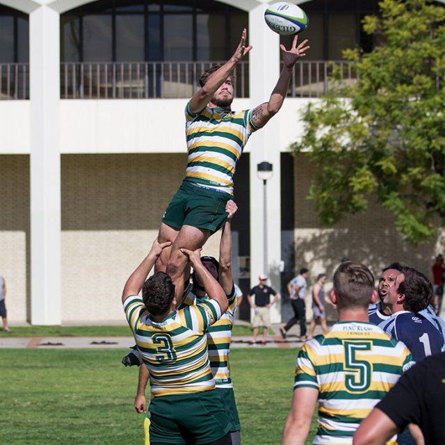 A PLNU Rugby Club athlete is lifted up by two of his teammates in order to catch the ball flying through the air.