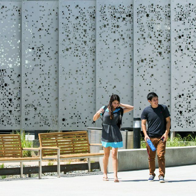 Two students walking down the campus mall with the science building panels behind them