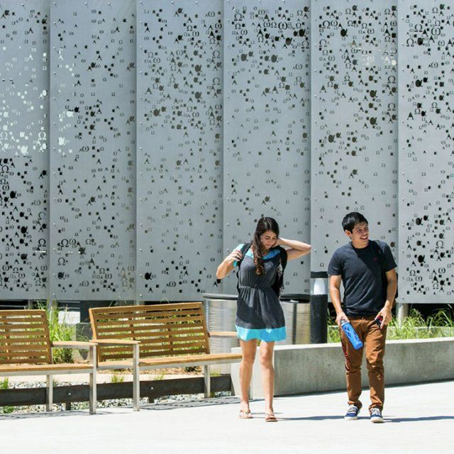 A male and female student walk to class during a sunny summer day