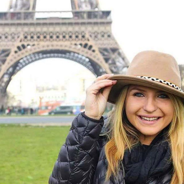 A PLNU student takes a photo in front of the Eiffel Tower in France.
