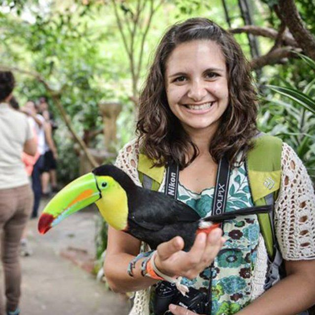Student holds a Toucan while studying abroad