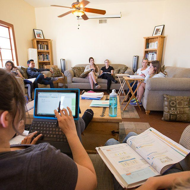 A group of students sit in a living room and have class as part of the community classroom experience