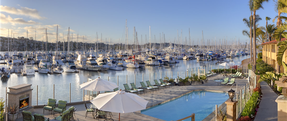 Soft light illuminates a pool overlooking a marina full of sailboats