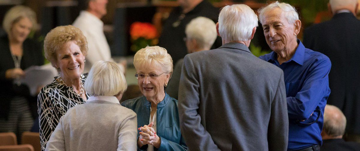A group of older PLNU alums greet each other and catch up in Brown Chapel during Homecoming
