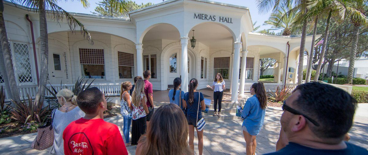 A PLNU tour guide speaks to a group in front of Mieras Hall