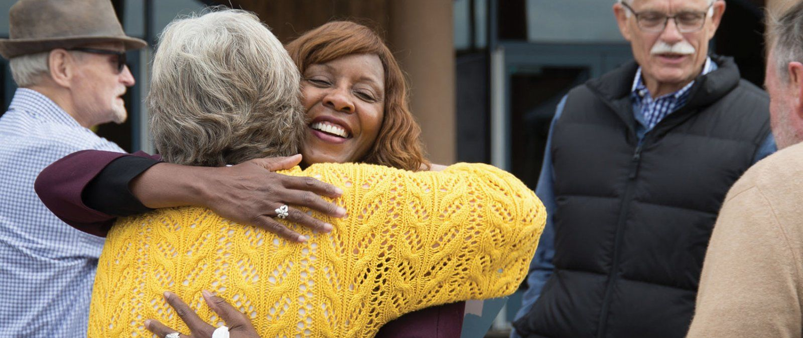 Two PLNU alumni greet each other with a hug during Homecoming