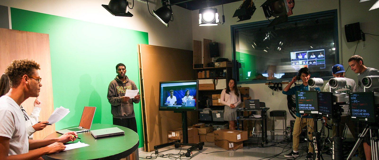 A group of students do a rehearsal for a Point TV broadcast within the production studio.