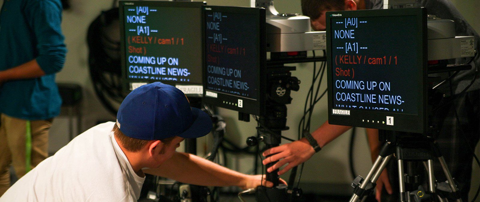 A male student helps rig a camera and screen for the anchors to use during a Point TV studio recording.