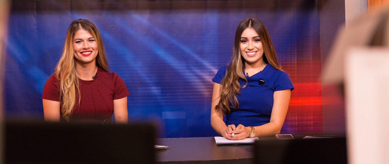 Two female students tv hosts smile as the camera begins recording.