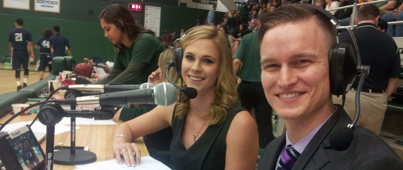 A female and male student broadcasters take in a basketball game.
