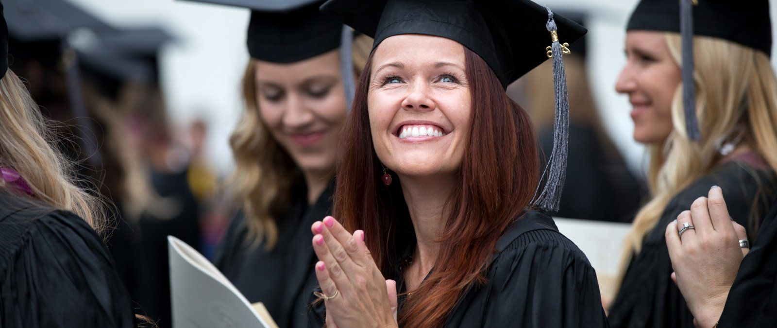 A female PLNU student smiles to the crowd at graduation