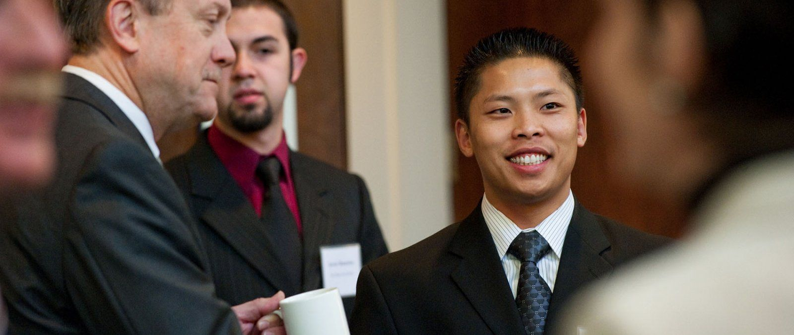A professionally dressed business student networks with working professionals at a PLNU business event