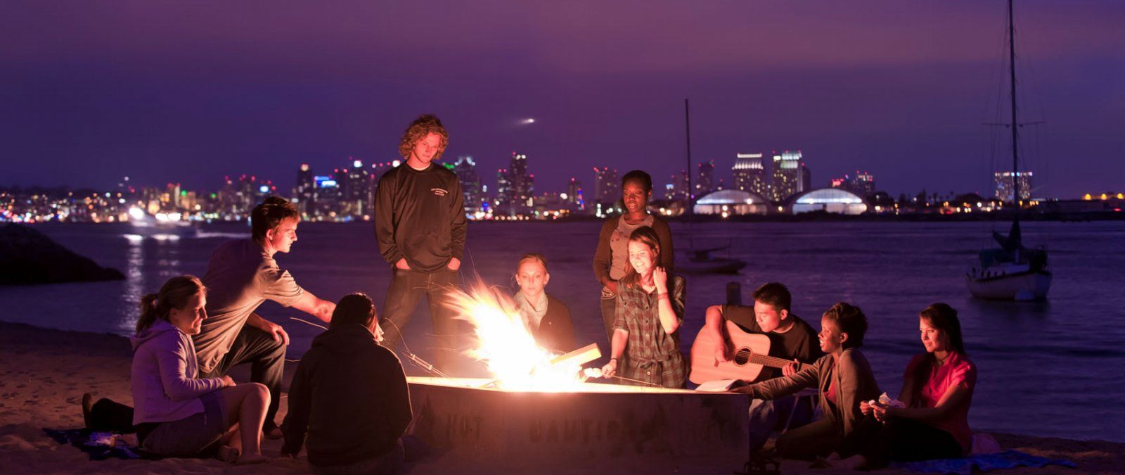 A group of PLNU students have a beach bonfire at night and sing worship music while at Shelter Island in San Diego