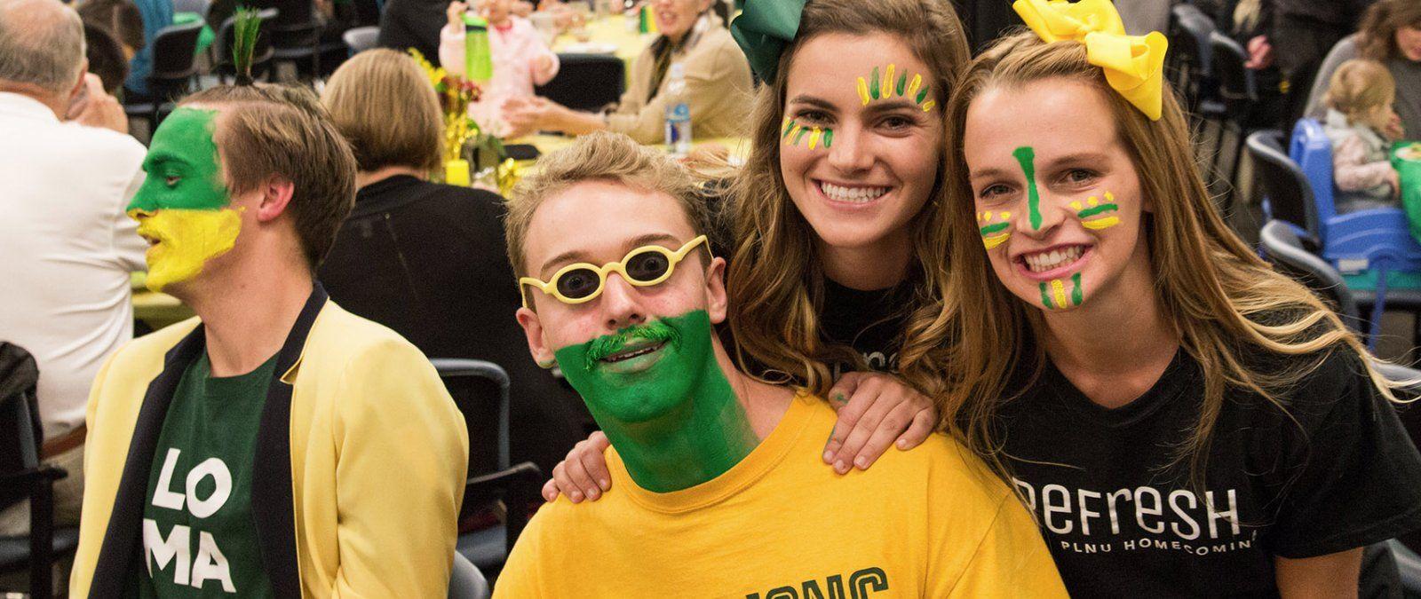 A group of students decked out in green and gold clothing and faces fully painted cheer on PLNU basketball teams during Homecoming