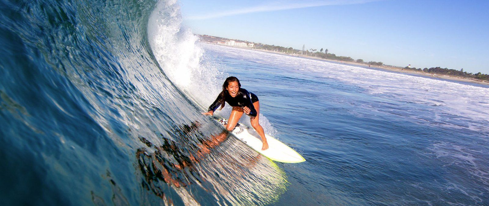 A PLNU female student surfs on a curling wave in San Diego