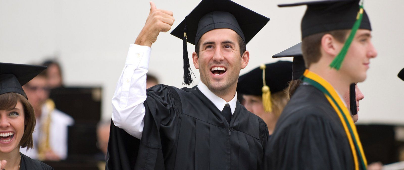 A graduating senior gives a thumbs up to his family in the audience